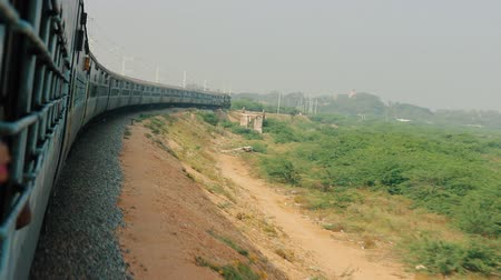 sleepers : Indian Railways. Train goes around arc area of dry Bush. Beautiful sight of turning of train from rear carriage Stock Footage