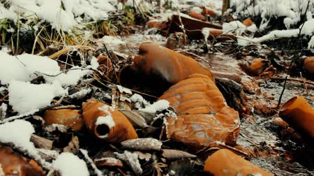 rivulet : Pollution of nature with plastic. Plastic bottles and cans in creek covered with red patina iron Stock Footage