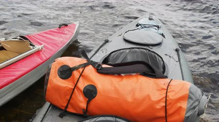 remo : Kayaks at beginning of passing on river (lower boat into water). Things stacked in waterproof bags Stock Footage