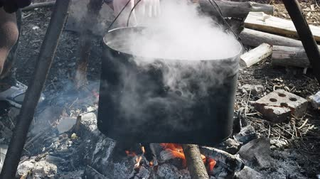 simmer : Field kitchen. Cooking on fire during hike.  Pot hanging over fire Stock Footage