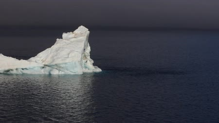 carrancudo : Impressive contrast. White iceberg on background of sullen waters of Arctic ocean and cloudy polar skies