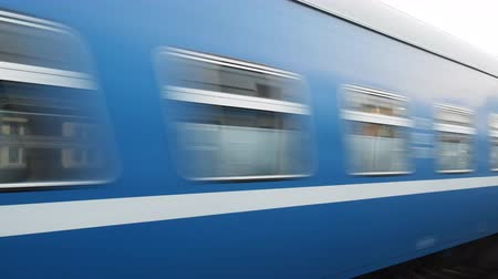 stopping : Blue passenger train, fast train rushes past  camera, shooting from below and side