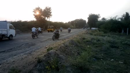otoyol : India, Tiruvannamalai  - January 17, 2016:  Road of India 5. Side view on secondaries broken road, a lot of motorcyclists