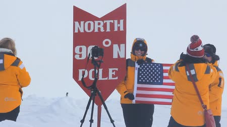 índice : Russia, North pole - 15 July 2016: Best Arctic journey. Entertainment tourists. Pointer of geographical North pole poit where all longitude and 90 degrees latitude. American tourists takes picture with stars and stripes