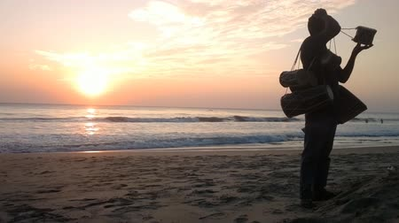 трейдер : India, Kerala - December 27, 2015: Bright tropical sunset. Merchant of drums (mridang, mrdanga) on beach. The Arabian sea