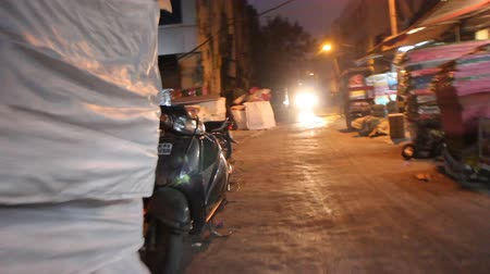Дели : India, new Delhi - 17 Dec, 2015: Goods, shops, and rickshaws in evening streets of Delhi. Shooting in front of operator Стоковые видеозаписи