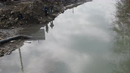 industrial fishing : Life in antropogenic landscape. Unpretentious urban anglers on shore of dug mudy canal Stock Footage