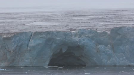 príncipe : midst of summer 900 km from North pole. Its snowing, temperature is around zero. Huge glacial grotto (ice caverns) at 50 m in wall of sheet glacier on island Prince Rudolf. Franz Joseph Land