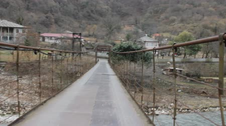 planking : Hanging bridge across mountain river. Camper is on bridge (camera is in front of him). Bridge is swinging, hesitation, vacillation, wavering, Caucasus, Abkhazia, village Tkvarchal