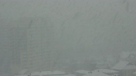 peril : Wall of falling snow. Powerful snowfall in city, snow storm. Clumps of snow fall from sky. Caucasus region, sudden cold