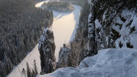 outlier : Weathering pillars (circumdenudation mountain) on Siberian river. Beautiful winter panorama of frozen river and Northern fir forests. Stone outcrops in form of pillars with height of up to 20 meters