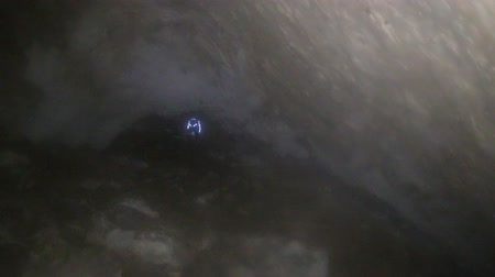 terra : Through misty cave. In front and below is seen cave explorer with flashlight. In cave is very high humidity and light diffusion Stock Footage