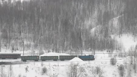 şartlar : freight train moving through coniferous forest during snowfall along frozen river among hills. Northern country. Side fron top Stok Video