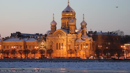russo : Northern city in blue frosty twilight. Illuminated Cathedral, gulls on frozen Neva river. S-Petersburg, Russia