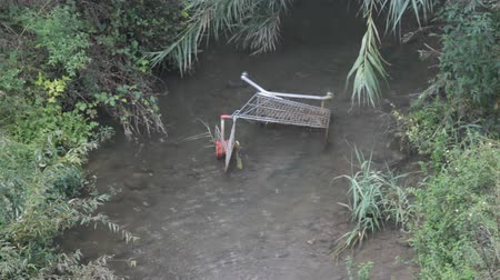 обязательство : Supermarket trolley (shopping basket, shopping cart) in muddy creek, its raining. Symbol of end of global trade, concept end of society insane consumption, large shopping, buying unnecessary things