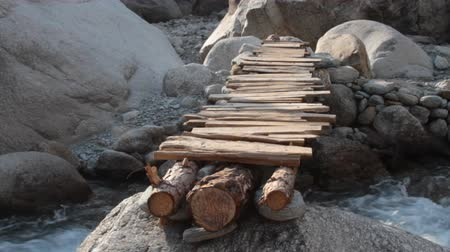 rivulet : Wooden temporary bridge over mountain stream. Bridge of logs and boards made after decline of water in rivulet and thrown from one block to another, river crossing, cross river, mountain path