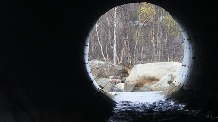 excesso de trabalho : Drainage pipe under the highway (culvert). Filming inside the pipe. Noise is water Stock Footage