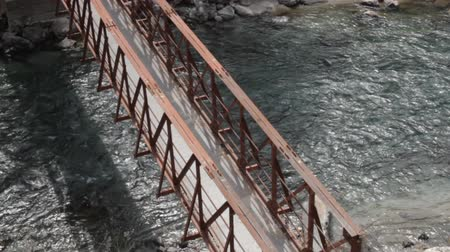 moloz : Metal pedestrian bridge over mountain river, view from the top