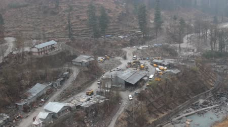 enredo : Snowfall over mountain village. Reduction of slopes from landslides, valley of river Parvati, India. Machinery for construction of building structures Stock Footage
