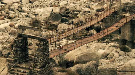pingente : Suspension bridge over river, pendant bridge, monkey bridge. Winter, bottom of the river Valley of the River Parvati, During the monsoon rains it is mad river. Himalayas