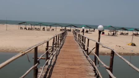 malabar coast : bamboo suspension bridge on a sea spit and a sandy beach, beach with sunshades and sun loungers, relax on the beach. Shooting from a man walking on the bridge. Goa, Malabar coast, Arabian sea, India Stock Footage