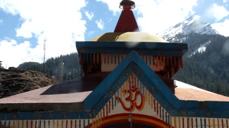 kultusz : mountain painted pagoda decorated with decorated with fabric canvases and brushes on the background of snow-capped mountains. India