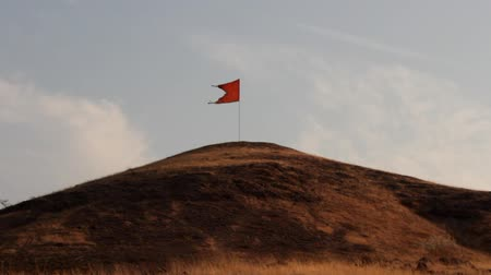 socialism : Red flag fluttering on the hill. View from a passing car Stock Footage