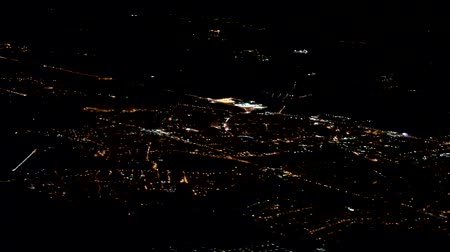 gastvrij : The night lights of the city twinkle in the dark under the wing of the plane, night flight Stockvideo