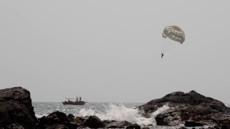 gale : Parasailing is an active form of recreation in Arabian sea, India, presence of a special parachute soars through the air over sea Stock Footage
