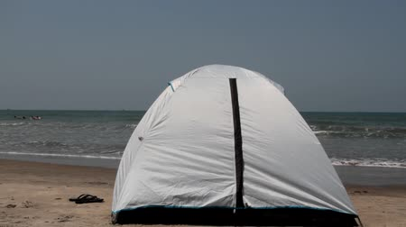 растворение : The white tent is set on the shore of the Arabian sea right in the surf zone. Sea holidays on the beach. The dissolution in the nature concept. Goa