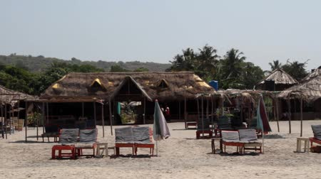 salone : Goa. Fenced off beach area with couch and lounge chairs and thatched bungalows, relax on the beach