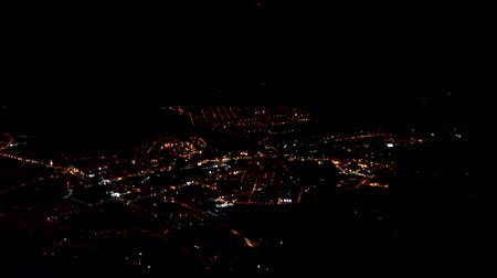 konuksever : The night lights of the city twinkle in the dark under the wing of the plane, night flight Stok Video