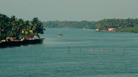 areca : Kerala backwaters. Fishing and pleasure boats. Fishing net stretched across a wide channel Stock Footage