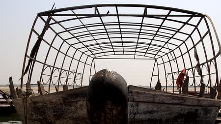rowboat : The boat stands in under a metal frame (boathouse) on the water of the Arabian sea. On the frame sit down Drongo Stock Footage