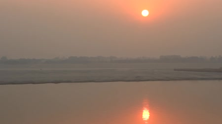 akşam vakti : Misty sunset over the calm winter river Ganges. Idyllic weather over a tropical river Stok Video