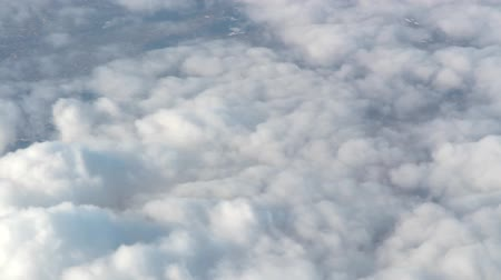 天窓 : Flying above the clouds. The plane flies over the Cumulus clouds. Villages are visible in the gaps of clouds 動画素材