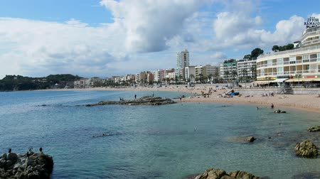 ziyafet : Spain, Lloret de Mar - October 2, 2017: tourist beach with palm trees hotels and vacationers in Mediterranean low season Stok Video