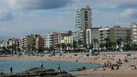 hordes : Spain, Lloret de Mar - October 2, 2017: tourist beach with palm trees hotels and vacationers in Mediterranean low season Stock Footage