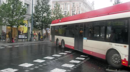 parisli : Lithuania, Vilnius - September 5, 2017: Trolleybuses and cars, passers-by with umbrellas on autumn rainy streets of the capital of Lithuania Stok Video