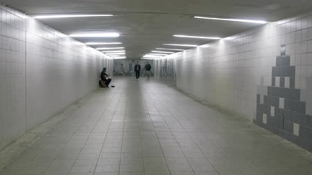Tallinn, Estonia - September 1, 2017: underground passage was almost empty, but the guitarist is trying to earn money public play, street musician
