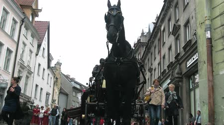 Tallinn, Estonia - September 1, 2017: Coach on old streets. Entertainment of citizens and tourists. Unusual perspective shooting from muzzle of horse up on carriage and people