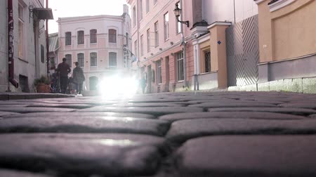 Tallinn, Estonia - September 1, 2017: Pavement in lower city. Unusual shooting with a very low camera position, large cobblestones and the effect of hitting cars