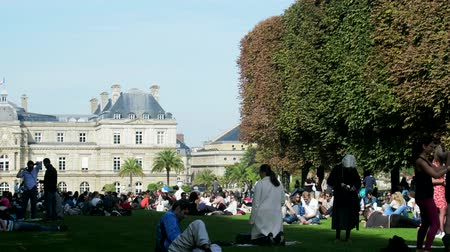 резидент : Paris, France - 24.09.2017: huge number of Parisians resting on lawn on summer day. Overpopulation of megacities and craving for nature, average man Стоковые видеозаписи