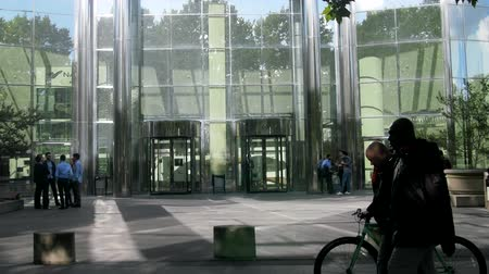 establishment : Paris, France - 24.09.2017: Business center, company office in La Défense and office workers in front of entrance with glass revolving door