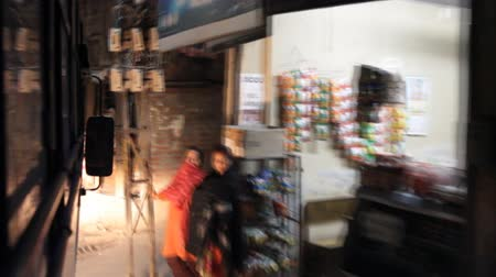 bazar : India, Himachal Pradesh- March 16, 2018: Night trading. Shooting through the window of the bus that moves through the narrow streets of the shopping district, retail mall Vídeos