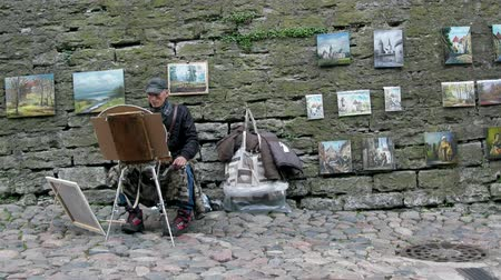 Tallinn, Estonia - September 1, 2017: Street artist (pavement painter) paints and sells his paintings in the old part of the city