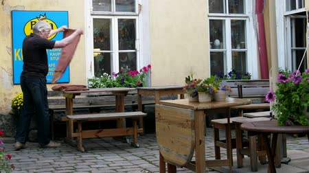 Tallinn, Estonia - September 1, 2017: street art cafe is closing. The waiter folds the tablecloth