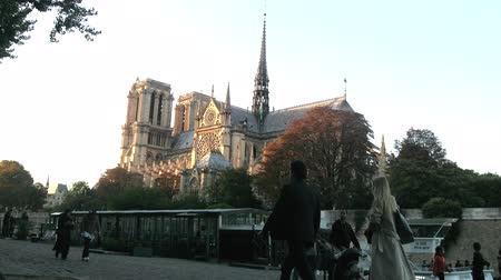 Paris, France - 24.09.2017: Notre Dame de Paris temple at sunset, Parisians people and river trams with tourists Wideo