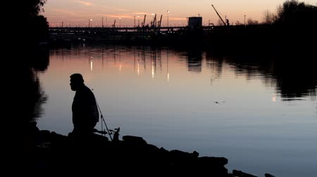 unutulmayan : City fishing. Fishermen late at night on the banks of the city river at sunset and a huge road junction with lights and cars. Recreation area and mens leisure