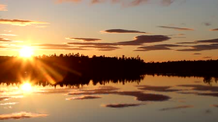águas : Polar night, midnight sun over forest calm lake. Never setting sun, sky with gently illuminated clouds that are reflected in mirror of waters. Great weather and view creates pleasant mood